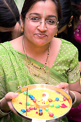 Woman holding out an offering of candles and sweets in celebration of Navratri; the Hindu festival of Nine Nights,