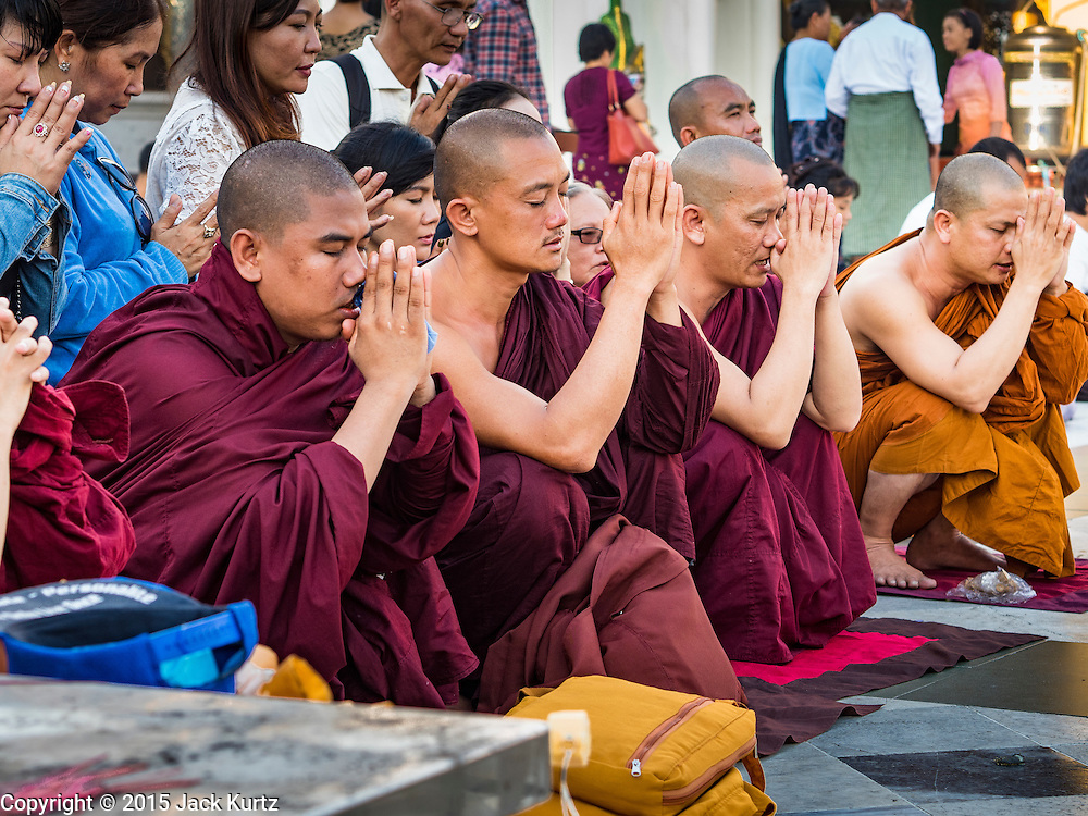 31 OCTOBER 2015 - YANGON, MYANMAR: Burmese Buddhist monks lead prayers at Shwedagon Pagoda. Some members of the Burmese Sangha (brotherhood of monks) have inserted themselves into Myanmar's election campaign. Members of Ma Ba Tha, an organization of nationalist conservative monks, have come out in opposition to Aung San Suu Kyi and her National League for Democracy (NLD), saying she is too friendly with Myanmar's Muslim minority and would not be able to govern Myanmar. Shwedagon Pagoda is officially known as Shwedagon Zedi Daw and is also called the Great Dagon Pagoda or the Golden Pagoda. It is a 99 metres (325ft) tall pagoda and stupa located in Yangon, Burma. The pagoda lies to the west of on Singuttara Hill, and dominates the skyline of the city. It is the most sacred Buddhist pagoda in Myanmar and contains relics of four past Buddhas: the staff of Kakusandha, the water filter of Koṇāgamana, a piece of the robe of Kassapa and eight strands of hair from Gautama, the historical Buddha. The pagoda was built between the 6th and 10th centuries by the Mon people, who used to dominate the area around what is now Yangon (Rangoon). The pagoda has been renovated numerous times through the centuries. Millions of Burmese and tens of thousands of tourists visit the pagoda every year, which is the most visited site in Yangon.      PHOTO BY JACK KURTZ