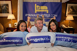 © Licensed to London News Pictures. 31/10/12 Airline Ryanair is to expand its operations and create an estimated 1000 jobs at airports in Liverpool, Manchester and the East Midlands. File picture dated 18/04/2012. CEO of Ryanair Michael O'Leary (centre) posing with Ryanair cabin crew Carla Dominguez (left) and Ornella Matrisciano (right) to promote the launch of ryanairhotels.com, a hotel comparison website, at the Rubens Hotel in London.  Photo credit: Tolga Akmen/LNP