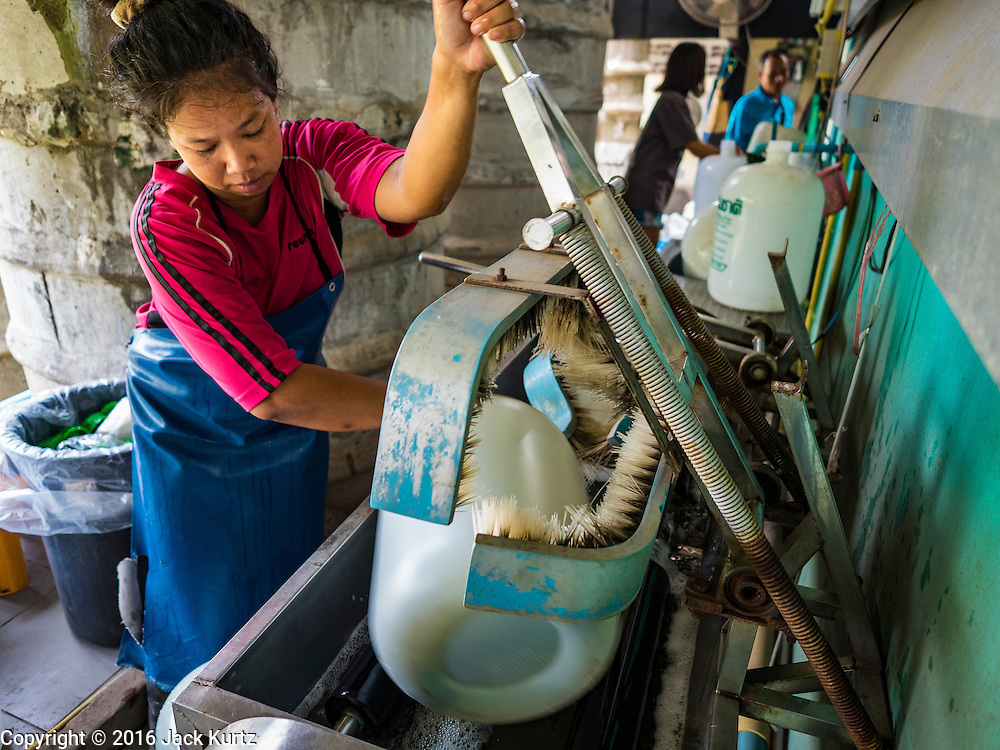 16 MARCH 2016 - BAN SONG, PRACHIN BURI, THAILAND: A worker cleans bottles at a water bottling plant in Ban Song. The plant has been open for 11 years and is reporting that demand has increased above normal this year because more people are buying bottled water because salt water has intruded into the local water supply. Some people are buying the bottled water to wash and bathe with because of the salt water intrusion. The drought in Thailand is worsening and has spread to 14 provinces in the agricultural heartland of Thailand. Communities along the Bang Pakong River, which flows into the Gulf of Siam, have been especially hard hit since salt water has intruded into domestic water supplies as far upstream as Prachin Buri, about 100 miles from the mouth of the river at the Gulf of Siam. Water is being trucked to hospitals in the area because they can't use the salty water.    PHOTO BY JACK KURTZ