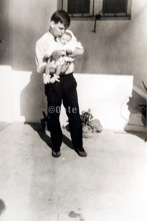 young father holding and kissing baby toddler ca 1960s