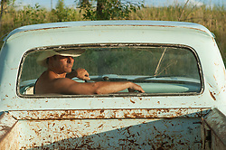 handsome man without a shirt in a pickup truck