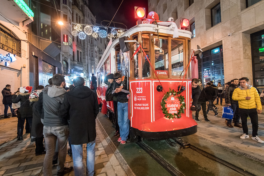 Passengers grip onto the sides of trolley car as it makes it way through the busy streets of Istanbul, Turkey