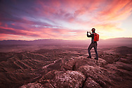 A person with a smartphone stands on a precipice and takes a photo from Font's Point in Anza Borrego, California.