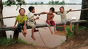 Ban Khinak, Laos-- Aug 20, 2004  Children from the   village of Ban Khinak, which sits along the Mekong River and just north of the  Khone Falls,  kid around as  adults go about their business at a nearby fish market.   photo by essdras m suarez/glboe staff      Library Tag 11282004   National/Foreign    Page One
