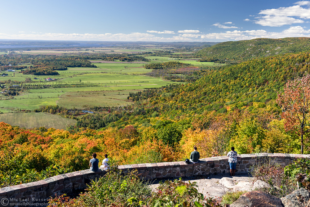 Tourists take in the view from the Champlain Lookout at Gatineau Park in Chelsea, Québec, Canada. The Champlain Lookout is located on the edge of the Eardley Escarpment which is the dividing line between the Canadian Shield and the St. Lawrence Lowlands.
