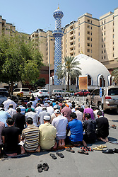 Many men praying on Friday outside mosque at Burjuman shopping centre in Dubai United Arab Emirates
