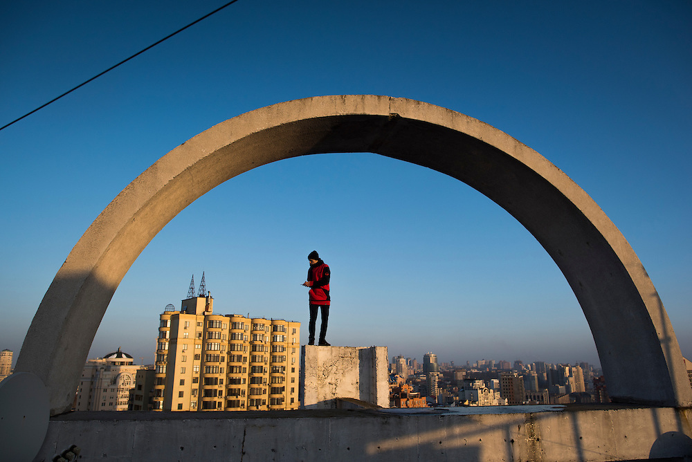 Extreme climber Mustang Wanted takes photos while posing for a portrait on the roof of a 26-storey building on February 19, 2017 in the Shevchenkovski District of Kiev, Ukraine.