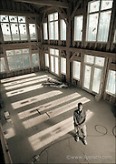 An architect stands inside a large sunlit room he designed.