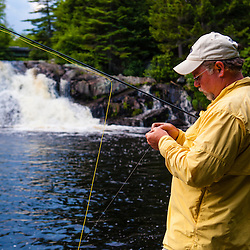A man fly-fishing for brook trout below Upper Cold Stream Falls in Maine's Northern Forest. Johnson Mountain Township.