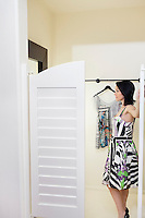 Side view of a mid adult woman standing at doorway of dressing room in fashion boutique