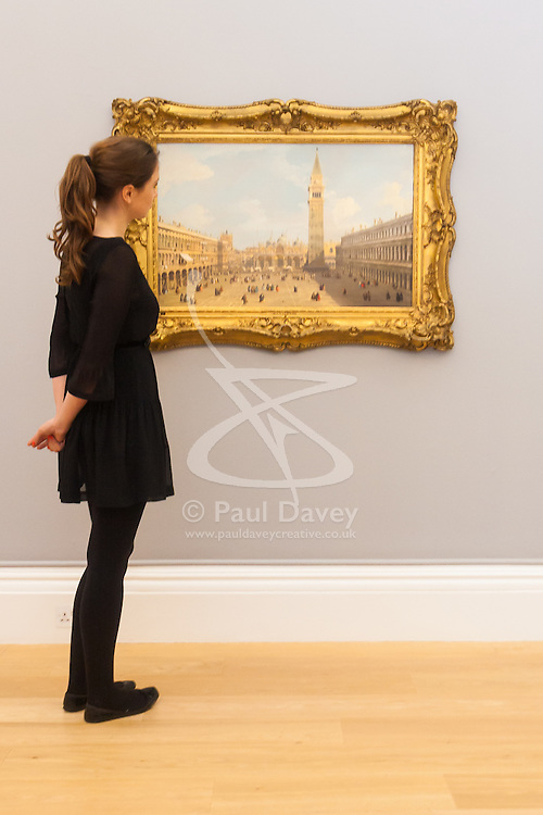Sotheby's London, November 28th 2014.Sotheby's hold a preview for their December 3rd sale of Old Master and British Paintings at their Bond Street gallery. The exhibition runs from November 29th to December 3rd. PICTURED: A woman admires  Canaletto's Venice, the Piazza San Marco Looking East Towards the Basillico, which is expected to fetch up to £7 million at auction.