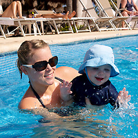 A young mother playing with her son in a resort pool.