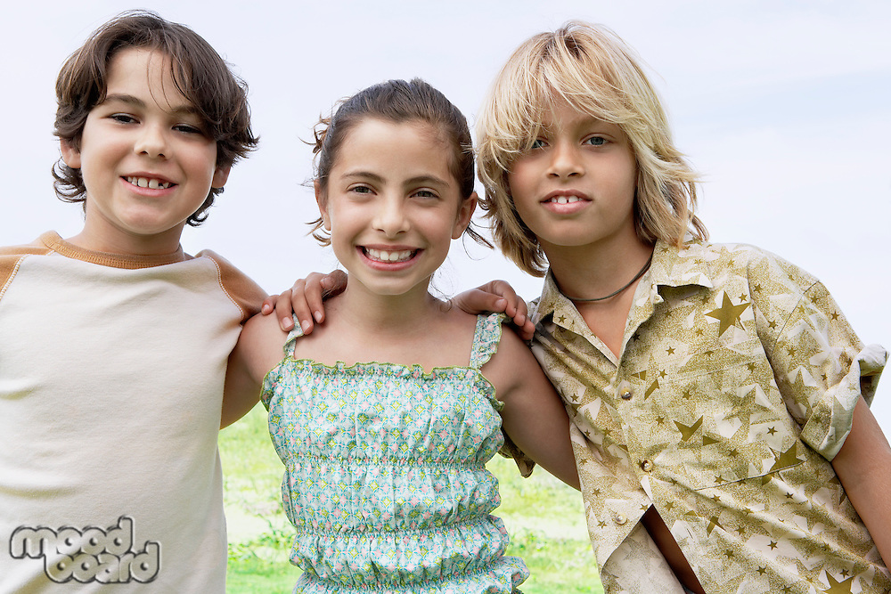 Smiling pre-teen Friends standing side by side outside arms around