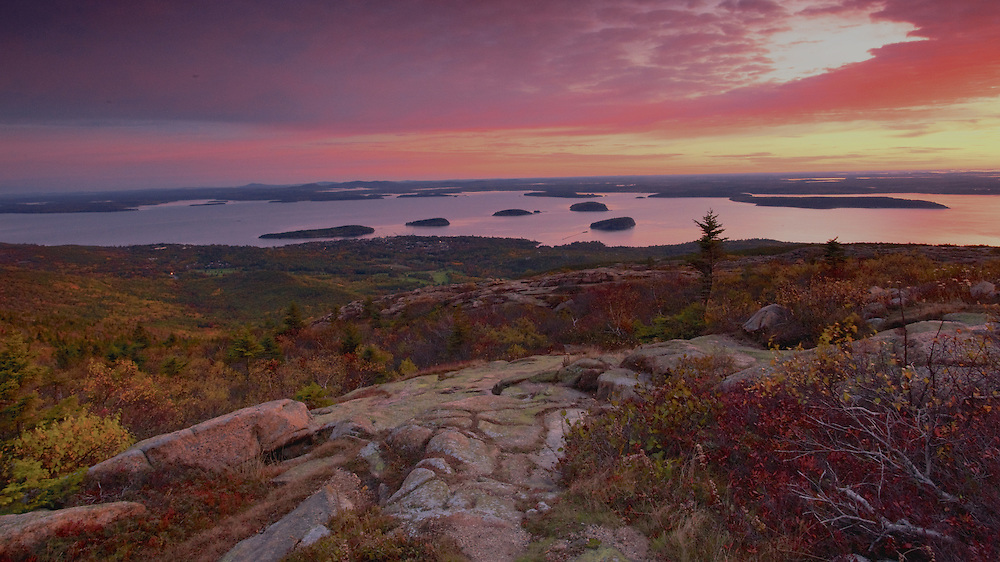 For much of the year, Cadillac Mountain in Acadia National Park, Maine is the first to receive the rays of the morning sun. No visit to the park is complete without watching the sunrise from the the summit. The town of Bar Harbor and the islands of Frenchman's Bay are visible in the distance.