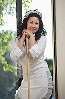 Portrait of young housemaid standing with mop