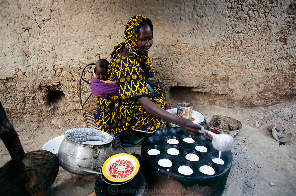 (MODEL RELEASED IMAGE). In the predawn light, with little Tena bundled onto her back, Fatoumata Toure crouches in the street outside her apartment and lights a fire under the griddle she uses to cook ngome, thick pancakes made from finely pounded corn or millet flour, oil, and salt. Her house is only a minute's walk from the larger home of her co-wife Pama Kondo. Fatoumata repeats this streetside routine every day except Saturday, when she sells ngome breakfast cakes at the village market. Hungry Planet: What the World Eats (p. 211). The Natomo family of Kouakourou, Mali, is one of the thirty families featured, with a weeks' worth of food, in the book Hungry Planet: What the World Eats.