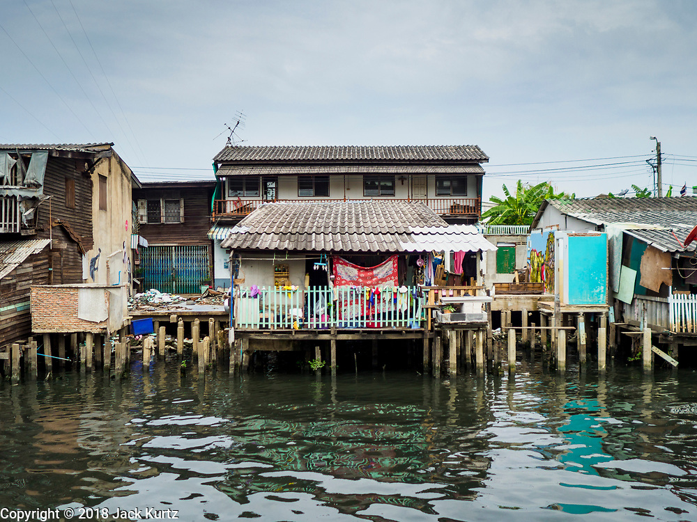 "22 MARCH 2018 - BANGKOK, THAILAND: A remaining home on Khlong Lat Phrao flanked by homes that have been demolished. Bangkok officials are evicting about 1,000 families who have set up homes along Khlong  Lat Phrao in Bangkok, the city says they are ""encroaching"" on the khlong. Although some of the families have been living along the khlong (Thai for ""canal"") for generations, they don't have title to the property, and the city considers them squatters. The city says the residents are being evicted so the city can build new embankments to control flooding. Most of the residents have agreed to leave, but negotiations over compensation are continuing for residents who can't afford to move.      PHOTO BY JACK KURTZ"