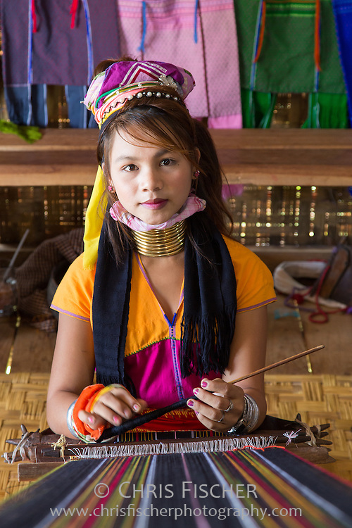 "A young Padaung ""long-necked"" woman weaving in a shop on Inle Lake. Around the age of five the first brass coils are applied, and as the girls grow older, longer coils are added. The weight of the brass presses down the collar bone and compresses the rib cage, which gives the appearance of a very long neck."
