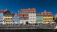Colourful buildings, cafes and restaurants in the tourist district of Nyhavn, Copenhagen, at the height of summer