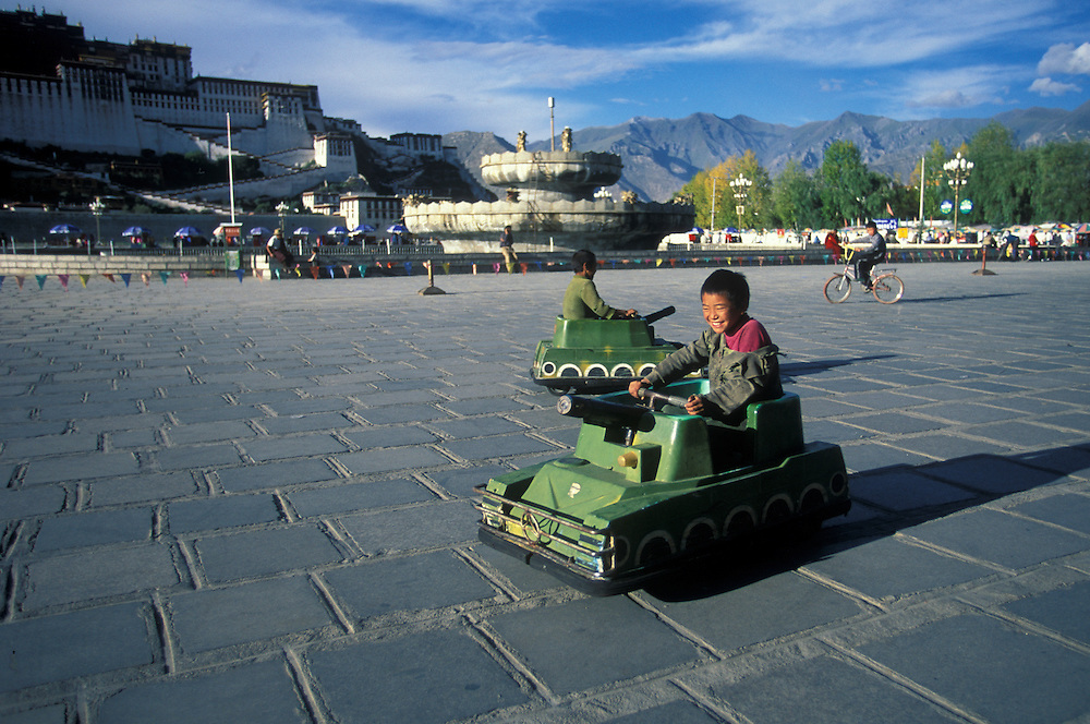 Chinese children playing in toy tanks in front of the Potala Palace, Lhasa, Tibet