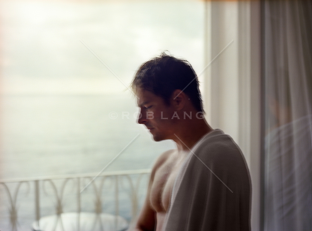 man without a shirt leaning against a balcony window