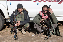 © Licensed to London News Pictures. 11/12/2014. Sinjar Mountains, Iraq. Two Yazidi peshmerga fighters sit on their haunches at a base on the top of Mount Sinjar.<br /> <br /> Although a well publicised exodus of Yazidi refugees took place from Mount Sinjar in August 2014 many still remain on top of the 75 km long ridge-line, with estimates varying from 2000-8000 people, after a corridor kept open by Syrian-Kurdish YPG fighters collapsed during an Islamic State offensive. The mountain is now surrounded on all sides with winter closing in, the only chance of escape or supply being by Iraqi Air Force helicopters. Photo credit: Matt Cetti-Roberts/LNP