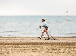 THEMENBILD - eine Spaziergängerin mit Walkingstöcke am Strand. Lignano ist ein beliebter Badeort an der italienischen Adria-Küste, aufgenommen am 15. Juni 2019, Lignano Sabbiadoro, Italien // a walker with walking sticks on the beach. Lignano is a popular seaside resort on the Italian Adriatic coast on 2019/06/15, Lignano Sabbiadoro, Italy. EXPA Pictures © 2019, PhotoCredit: EXPA/ Stefanie Oberhauser