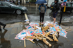 London, UK. 19 July, 2019. Placards intended for the Youth Strike for Climate lie sodden in the rain on a day of heavy showers in Westminster.