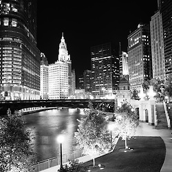 Chicago River skyline buildings at night in black and white by the Wabash Avenue bridge with Trump Tower, Wrigley Building, Hancock Building, and Equitable Building.