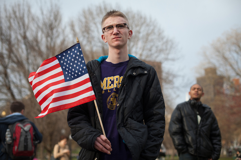 Emerson College student Kevin Cheetham of Oakland, NJ holds a flag  during a vigil for the victim's of Monday's terrorist bombings near the finish line of the Boston Marathon, on Boston Common in Boston, MA on Tuesday, April 16, 2013.  (Matthew Cavanaugh for The Washington Post)