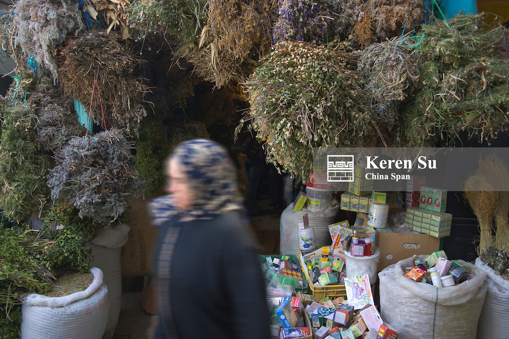 Woman passes by shop selling herbs on the market street in old medina, UNESCO World Heritage site, Tunis, Tunisia