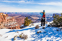 A woman taking photos of the spectacular view, Island In The Sky, Canyonlands National Park, Utah, USA.