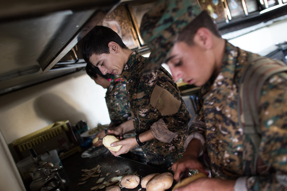 Members of Sinjar Resitance Units preparing food in a base near the battle zone. Shingal (Sinjar), Iraq, August 26, 2015