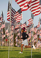 A girl runs through amongst 3,000 US flags are displayed at Pepperdine University to mark the 12th anniversary of the 9/11 terror attack, September 10, 2013 in Malibu, California. Photo by Ringo Chiu/PHOTOFORMULA.com)