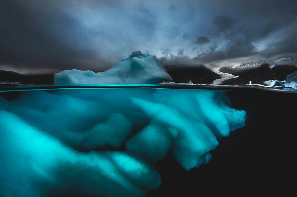 Iceberg at Norvestfjord with glacier valley Greenland
