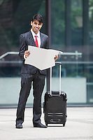 Young Indian businessman with luggage bag reading paper