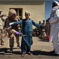 Spc. Brett Hamilton(307th Forward Support Battalion) use a metal detector on a young boy waiting to enter the medical clinic near Forward Operating Base Salerno in Afghanistan Tuesday, May 31, 2005. All patients entering the clinic were searched before entering.