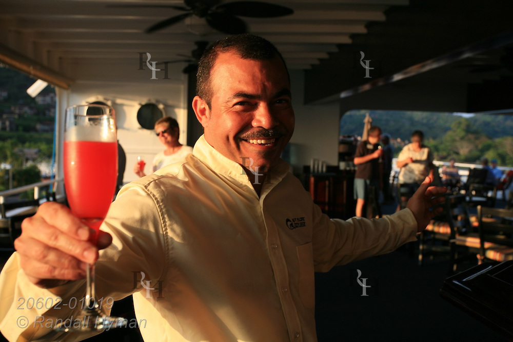 Waiter aboard Cruise West's ship, Pacific Explorer, offers drink; Costa Rica.
