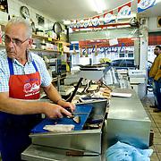 """Nederland Rotterdam 11 september 2007 .Allochtone klanten wachten terwijl de vis schoongemaakt wordt in vishandel Dick Selier. - Zwaanshals 307 - 010 - 466.68.87  in probleemwijk Oude Noorden. Vishandel Dick Selier heeft het assortiment aangepast aan de verschillende specifieke wensen van zijn, veelal, allochtone klanten. .Probleemwijk Oude Noorden Rotterdam is een van de 40 wijken waar het kabinet 2,4 miljard voor heeft gereserveerd in de miljoenennota om de problematiek in deze wijken het hoofd te bieden.  ?Het kabinet trekt in de begroting voor 2008 het meeste extra geld uit voor de 'onderkant' van de samenleving.in de miljoenennota 2007 trekt Justitie 34,6 miljoen extra uit voor het terugdringen van de jeugdcriminaliteit. Voor inburgering en integratie wordt 80 miljoen extra uitgetrokken. Justitie is in totaal 360 miljoen euro kwijt aan uitvoering van de pardonregeling voor een oude groep asielzoekers. De woningcorporaties dragen 2,5 miljard bij aan de probleemwijken. Het rijk stelt 500 extra wijkagenten beschikbaar. Corporaties steken 2,5 miljard in probleemwijken.De woningbouwcorporaties gaan de komende tien jaar 2,5 miljard euro investeren in de aanpak van de veertig probleemwijken. Dat staat in een akkoord dat minister voor Wonen, Wijken en Integratie Ella Vogelaar (PvdA) maandag heeft bereikt met de koepel van de woningcorporaties Aedes. De koepel had de gesprekken eerder opgeschort uit onvrede over de eenzijdige beslissing van het kabinet om de corporaties een belastingverhoging op te leggen..Over de belastingverhoging is nu nog geen besluit genomen. Het nieuwe akkoord tussen Vogelaar en Aedes zorgt voor de oprichting van een fonds waarin alle Nederlandse woningcorporaties jaarlijks, naar draagkracht, in totaal 250 miljoen storten. In tien jaar leidt dat tot een kapitaal van 2,5 miljard. De woningcorporaties houden dat geld wel in eigen beheer. """"We hebben echt een doorbraak bereikt"""", stelde een vrolijke Vogelaar maandag..Volgens de minister kunnen de veert"""