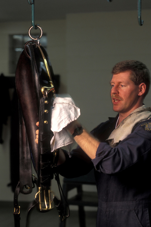 Canada, Ontario, Ottawa, Constable Paul Marleau cleans horse tack at RCMP Equitation Centre