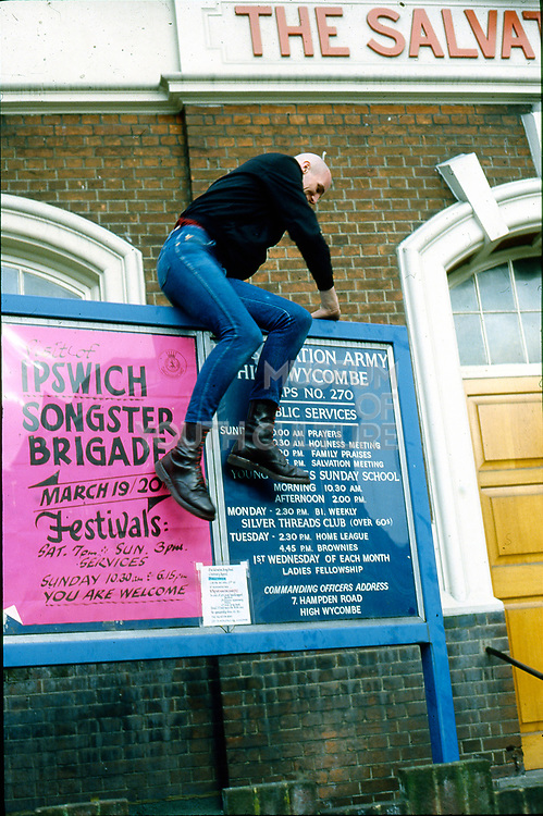 Mark Goddard climbing a church noticeboard, High Wycombe, UK, 1980s