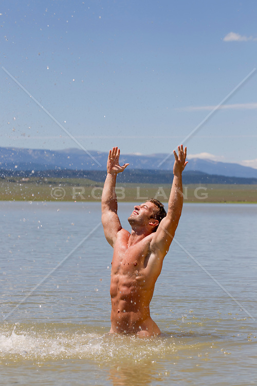 good looking shirtless man splashing water while standing in a beautiful lake in New Mexico