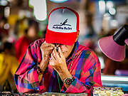24 DECEMBER 2018 - CHANTABURI, THAILAND:  A man looks at an amulet in the amulet market in Chantaburi. Chantaburi is the capital city of Chantaburi province on the Chantaburi River. Because of its relatively well preserved traditional architecture and internationally famous gem market, Chantaburi is a popular weekend destination for Thai tourists.   PHOTO BY JACK KURTZ