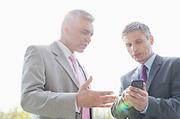 Businessmen discussing over mobile phone outdoors