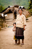 Laos, Luang Nam Tha. Khamu woman and a little from Ban Nam Pick.<br /> <br /> The Khamu arrived in northern Laos and Thailand in the early first millennium AD, making them one of the earliest inhabitants in the region. When the Lao arrived in the area they pushed the Khamu out of the valleys into higher land. <br /> <br /> Traditional Khamu villages can be found in low mountainous areas and forest valleys. The houses are built on low wooden stilts about 1 to 1.5 meters above the ground. The walls are made of bamboo mats without windows, the roof is covered with thatch. Traditional Khamu villages have a communal house, where young adolescent boys live and where men gather for important discussions or to work together on crafts. <br /> <br /> They cultivate rice, maize, cassava, gourds, eggplants, peanuts and vegetables. Besides that Khamu grow tobacco and brew whisky for self-consumption. They keep a few buffaloes, cattle and goats. Pigs and poultry are kept in larger numbers. <br /> <br /> The Khamu believe in several spirits and every village has a guardian spirit. Spirit gates are erected over the entrance to Khamu villages and special houses are built to make sacrifices. The Khamu practice a form of ancestor worship. Every village has a shaman and several sorcerers. <br /> <br /> The Khamu have never engaged intensively in weaving and buy most of their cloths from others. <br /> The festive dress of a Khamu woman includes a long-sleeved dark vest open at the front, often with red hems, a dark based sarong with many colored strings or motifs and a kerchief. On ordinary days Khamu women wear the Lao-styled sarongs and ordinary blouses with a multitude of bright colors. The older women wear a headscarf, the younger women wear their hair bound up in a bun and leave it uncovered. they decorate themselves with silver and copper bracelets can be found on the arms and legs.