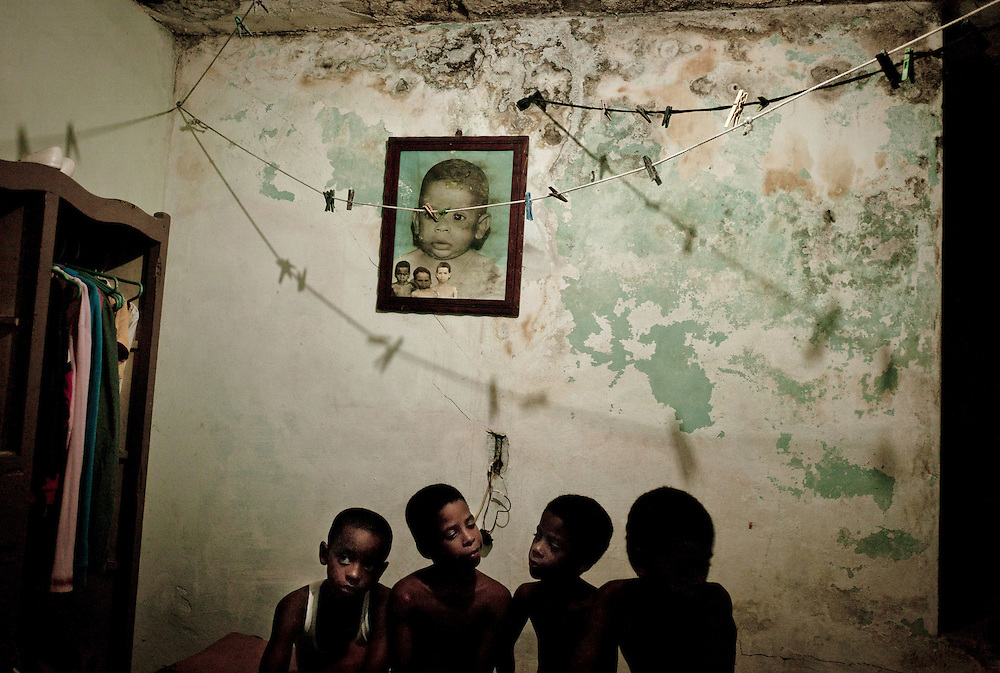 "Four brothers from the Morales family in their room, a ""barbacoa""  - or room built on the top of the main and only room of the house - where they have to share two bed with their mother. Centro Havana. All over the capital and in many provincial towns, Cubans are beginning to inject money into the island's ragged real estate, spurred by government measures to stimulate construction and a new law that allows them to trade property for the first time in 50 years. Photo/Tomas Munita"