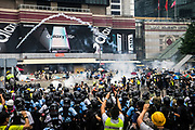Protesters toss tear gas canisters back at the police as they occupy roads in front of the Central Government Offices, during a protest against a proposed extradition law in Hong Kong, SAR China, on Wednesday, June 12, 2019. Hong Kong's legislative chief postponed the debate on legislation that would allow extraditions to China after thousands of protesters converged outside the chamber demanding the government to withdraw the bill. Photo by Suzanne Lee/PANOS