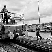 MIRAFLORES LOCKS - PANAMA CANAL<br /> Photography by Aaron Sosa<br /> Panama City, Panama 2012<br /> (Copyright © Aaron Sosa)<br /> <br /> From the outset, it was considered an important safety feature that ships were guided though the lock chambers by electric locomotives, known as mulas (mules, named after the animals traditionally used to pull barges), on the lock walls. These mules are used for side-to-side and braking control in the rather narrow locks (narrow relative to modern-day ships). Forward motion into and through the locks is actually provided by the ship's engines and not the mules'. A ship approaching the locks first pulls up to the guide wall, which is an extension of the centre wall of the locks, where she is taken under control by the mules on the wall before proceeding into the lock. As she moves forward, additional lines are taken to mules on the other wall. With large ships, there are two mules on each side at the bow, and two each side at the stern — eight in total, allowing for precise control of the ship.<br /> The mules themselves run on rack tracks, to which they are geared. Each mule has a powerful winch, operated by the driver; these are used to take two cables in or pay them out, to keep the ship centred in the lock while moving it from chamber to chamber. With as little as 60 cm (2 ft) of space on each side of a ship, considerable skill is required on the part of the operators.<br /> Smaller vessels, such as small tour boats and private yachts, are taken as handline transits, where mooring lines to the lock walls are handled manually by line handlers on the ship.