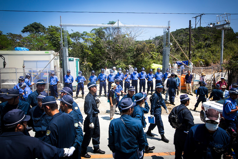 OKINAWA, JAPAN - AUGUST 19 : Police guard the gate from Anti U.S base protesters as they staged a sit-in protest against the construction of helipads in front of the gate of U.S. military's Northern Training Area in the village of Higashi, Okinawa Prefecture, on August 19, 2016. Japanese government resume construction of total six helipads in a fragile ten million year old Yanbaru forest that is home to endemic endangered species such as the Okinawan rail and Okinawan wood pecker. (Photo by Richard Atrero de Guzman/NURPhoto)